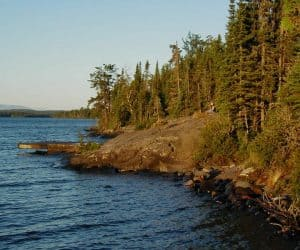 A lone camper sitting near the dock at Three Mile campsite at the edge of Rock Harbor, on Isle Royale. © 2002 Todd VerBeek.