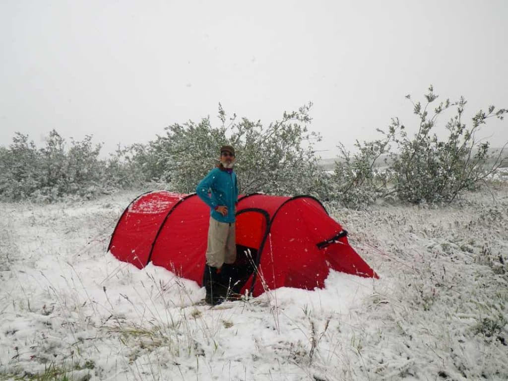 Brian Johnston stands next to his snow covered tent on July 20.